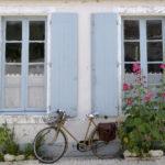Vélo garé devant une maison bordée de roses trémières